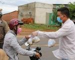 Bà con Nâm N'jang đứng dọc đường 14 gởi bắp luộc cho người về quê tránh dịch