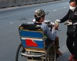 Người phụ nữ mang dép lê đi phát tiền giúp người về quê