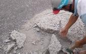 Hai thợ nề đục đẽo dẹp khối bêtông đổ giữa đường để xe không tai nạn