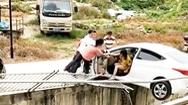 Video: Nữ tài xế lùi xe húc bay hàng rào, treo lơ lửng trên đường