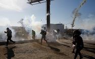 Mỹ bắn hơi cay đuổi người di cư trèo tường vượt biên