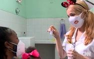 Y bác sĩ Cuba đeo băng đô chuột Mickey khi chích ngừa cho trẻ