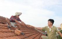 Thầy giáo leo mái nhà lợp ngói trường học sau bão