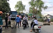 Bức xúc xe chở đất đá gây bụi, người dân mang gỗ, đá ra chặn