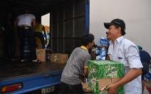 Xe chở nước giải khát lật, người dân giúp tài xế thu gom