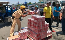 Xe tải ôm cua lật ngang, dân và cảnh sát gom nước ngọt giúp tài xế