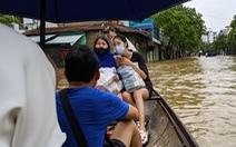 Nước lên nhanh, người dân bắt thuyền máy đi giữa TP Huế