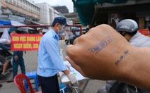 Đóng dấu 'đã khai báo y tế' lên tay người dân đi chợ