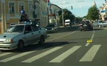 Người đi xe máy văng lên nóc taxi như phim