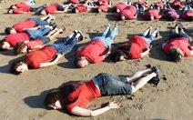 Nằm úp trên cát tưởng nhớ cậu bé Syria