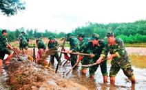 Bộ đội lội ruộng giúp dân