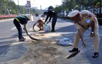 Cảnh sát giao thông phụ quét dọn cát giúp công nhân