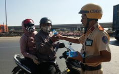 CSGT TP.HCM 'thổi còi' người đi xe máy để... tặng nước suối, khăn lạnh trên đường về tết