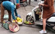 Người phụ nữ cán xe máy qua mẹt trái cây của chị bán hàng rong