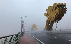Lái ôtô 'dìu' người đi xe máy qua cầu Rồng giữa mưa to, gió lớn