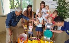 Hai nữ du khách Nga mắc kẹt tại Việt Nam bế con đi mua đồ cứu trợ dân vùng lũ