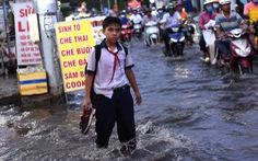 Triều cường dâng cao, học sinh, công nhân ở TP.HCM lội nước về nhà