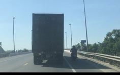 Xe máy chở 2 người núp bóng xe container để tránh nắng bất chấp nguy hiểm