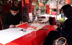 Ông đồ cho chữ qua tấm chắn chống dịch tại Hồ Văn