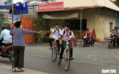 'Bà ngoại Hai' cầm bảng canh xe cho học trò qua đường an toàn