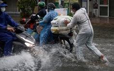 TP.HCM mưa trắng trời, nhân viên trực chốt đẩy xe dân qua chỗ ngập