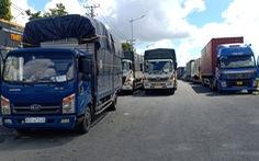 Hàng chục xe chở hàng thiết yếu bị kẹt tại chốt do quy định phải 'xuống hàng sang xe'