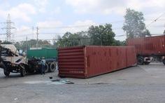 Một thùng container làm hai xe đầu kéo lật trong buổi sáng