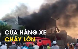 Người dân giúp chuyển xe máy ra khỏi cửa hàng xe cháy lớn