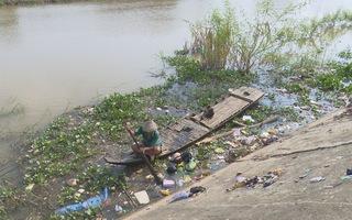 Lão nông bơi xuồng vớt rác thải nhựa mùa lũ