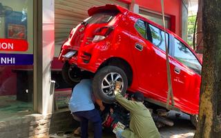 Video: Nữ tài xế lùi xe hơi đè xe máy, đâm sập tường trung tâm anh ngữ
