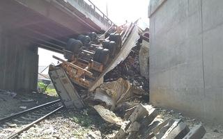 Video: Xe đầu kéo tông vào cầu vượt, rơi xuống đường sắt gây tê liệt giao thông