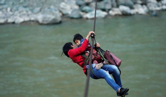 Thế giới trong tuần qua ảnh: Người mẹ ôm con đu dây qua sông